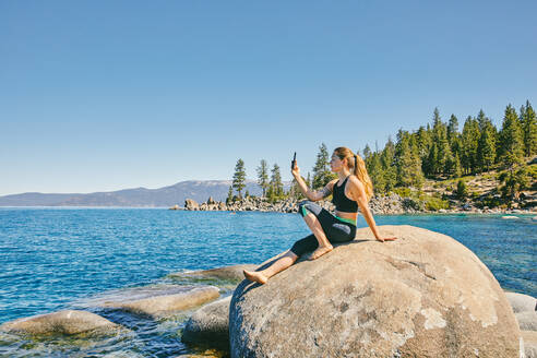 Young woman taking a picture of Lake Tahoe. - CAVF88895