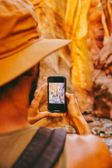 Young man wearing hat taking picture of slot canyons in Kanarra Falls - CAVF88904