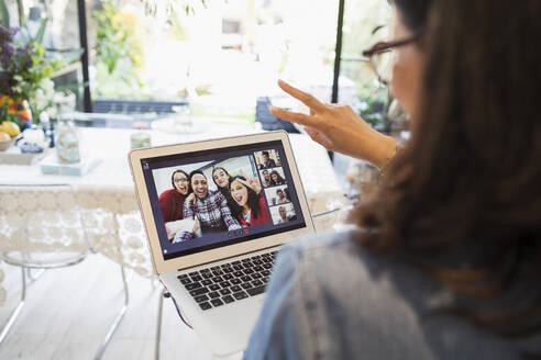 Woman video conferencing with family and friends at laptop screen - CAIF29512