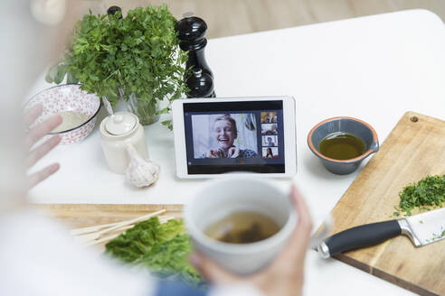 Woman drinking tea and cooking while video chatting with friends - CAIF29527