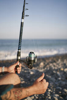 Close-up of mid adult man holding fishing rod at beach against clear sky during sunset - SASF00085