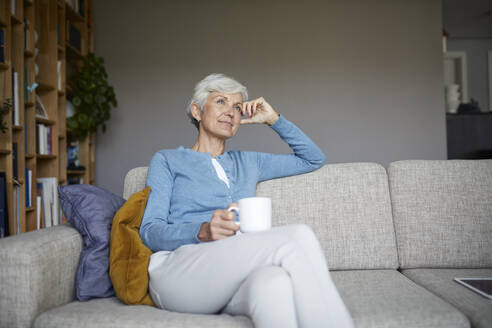 Thoughtful senior woman sitting on sofa holding coffee cup at home - RBF07794