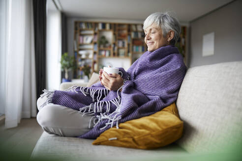 Thoughtful senior woman with blanket holding coffee cup while sitting on sofa at home - RBF07812