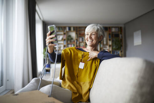 Smiling senior woman taking selfie with new blouse on smart phone while sitting at home - RBF07824