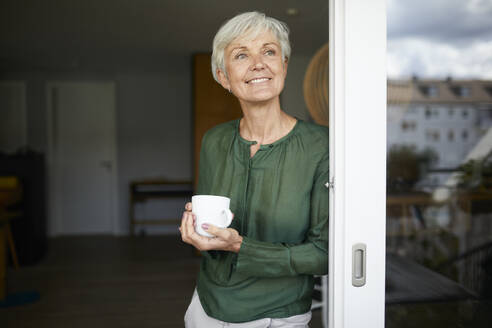 Senior woman standing with coffee cup by window at home - RBF07860