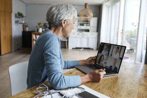Active senior woman attending meeting on video conference while sitting at home - RBF07869