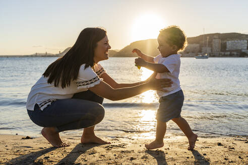 Cheerful mother playing with son at beach during sunset - DLTSF01202