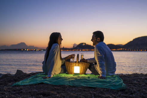 Couple with drinks looking at each other while sitting on beach against clear sky during dusk - DLTSF01211