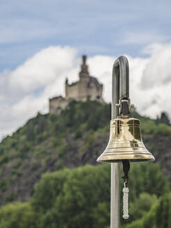 Germany, North Rhine-Westphalia, Braubach, Old-fashioned bell hanging outdoors with Marksburg castle in background - KEBF01647