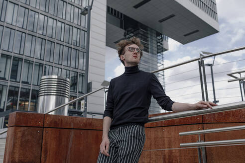Thoughtful young man looking away while standing by railing against building in city - OGF00567