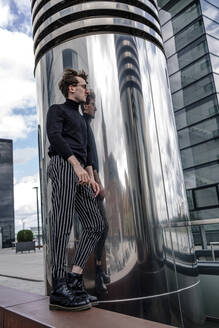 Thoughtful young man standing by modern column in city - OGF00573