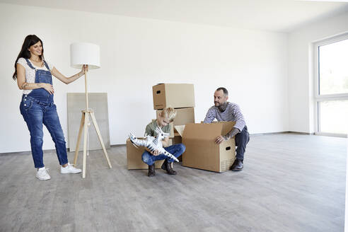 Pregnant mother holding electric lamp while father and son crouching on floor with toy and cardboard box - MJFKF00647