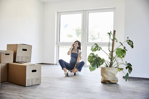 Thoughtful pregnant woman sitting on skateboard in house - MJFKF00659