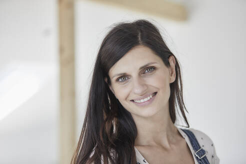 Smiling woman standing in new house - MJFKF00677