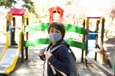 Boy wearing mask with backpack standing in schoolyard - VABF03463