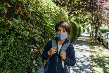 Schoolboy wearing mask looking away while standing by plants on footpath - VABF03469