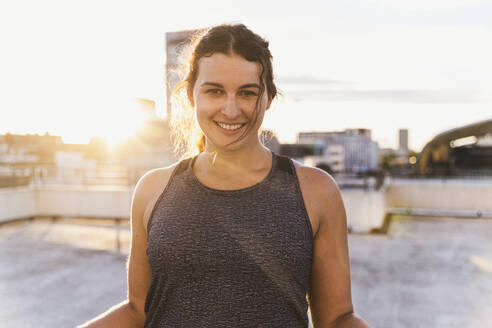 Smiling female athlete standing on building terrace against sky during sunset - UUF21410