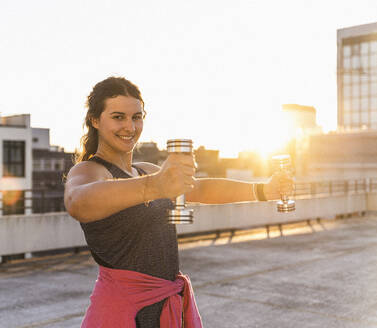 Smiling young woman exercising with dumbbells on terrace against clear sky at sunset - UUF21413