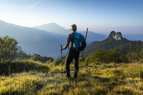 Male hiker with backpack looking at mountain against sky during sunrise, Orobie, Lecco, Italy - MCVF00590