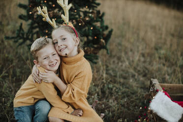 Smiling siblings embracing while sitting by Christmas tree on land - GMLF00597