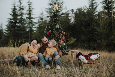 Smiling family sitting by Christmas tree on grassy land at countryside during sunset - GMLF00603