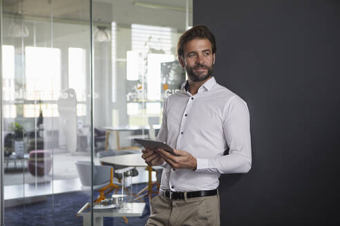 Businessman holding digital tablet while leaning on wall at office - RBF07878