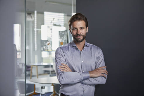 Confident businessman with arms crossed standing in office - RBF07905