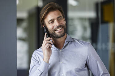 Smiling businessman talking on mobile phone in office - RBF07914
