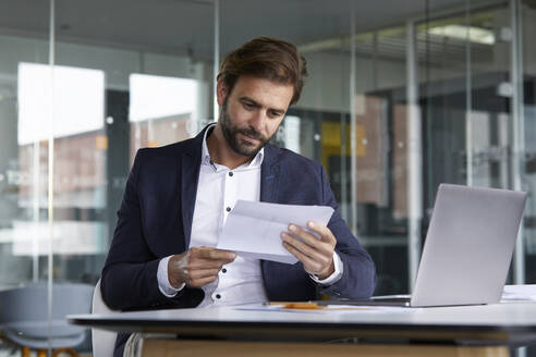 Businessman examining document while sitting in office - RBF07920