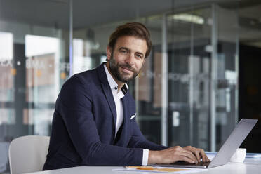 Businessman working on laptop while sitting by desk in office - RBF07923