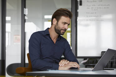 Man working on laptop while sitting in office - RBF07926