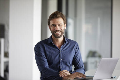 Smiling businessman using laptop while standing at desk in office - RBF07935
