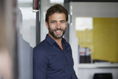 Man smiling while leaning on wall in office - RBF07938