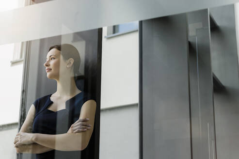 Thoughtful female entrepreneur with arms crossed standing in office seen through glass door - BMOF00412