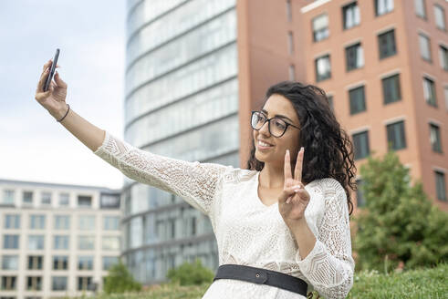 Smiling young woman showing peace sign while taking selfie with smart phone in city - BFRF02307