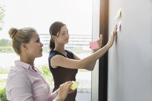 Female colleagues discussing over adhesive notes on wall in office - BMOF00420