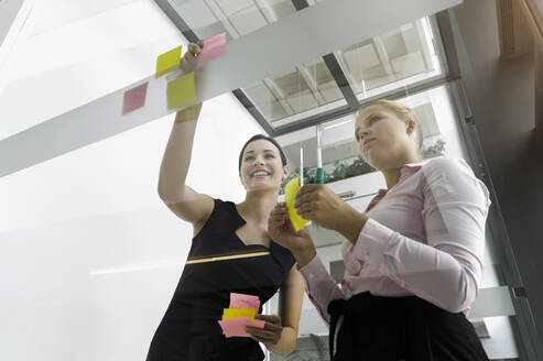 Female colleagues sticking adhesive notes on glass wall while standing in office - BMOF00429