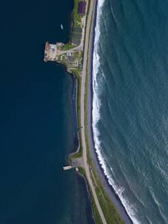 Russia, Primorsky Krai, Zarubino, Aerial view of coastal road stretching along narrow strip of land - KNTF05329