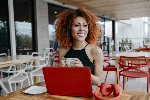 Smiling afro woman with laptop on table holding coffee cup while sitting at sidewalk cafe - DSIF00117