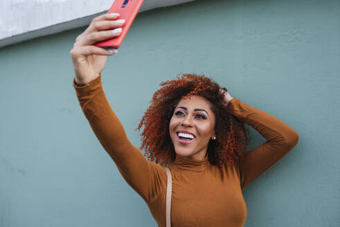 Cheerful afro young woman taking selfie with smart phone while standing by wall - DSIF00123