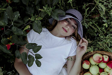 Mid adult woman wearing hat sleeping by apples on land in orchard - OGF00592