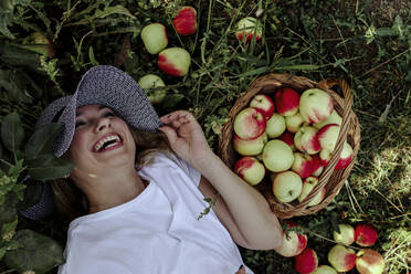 Mid adult woman wearing hat laughing while lying by apples on land in orchard - OGF00595
