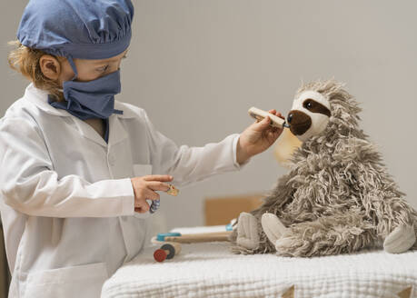 Young child in medical PPE examines a plush toy sloth and takes it's temperature with thermometer - CAVF89117