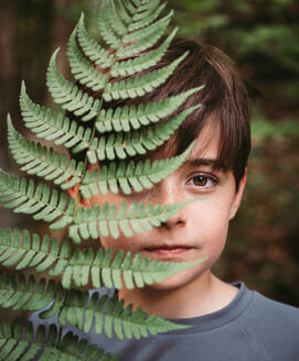 Portrait of young boy covering half of his face with a fern leaf. - CAVF89171