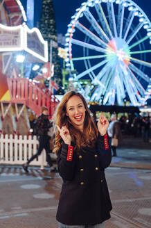 Cheerful woman gesturing while standing against illuminated Ferris wheel at night during Christmas - JMPF00399