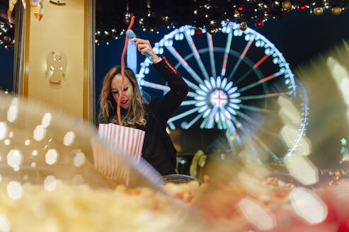 Woman buying jellybeans from illuminated market at amusement park during Christmas - JMPF00402