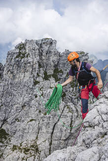 Mature man holding ropes while standing on European Alps, Lecco, Italy - MCVF00617
