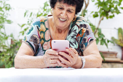 Close-up of smiling senior woman using mobile phone at table while sitting in yard - PGF00009