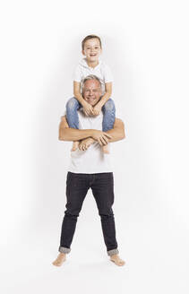 Father carrying son on shoulders while standing against white background - SDAHF00975