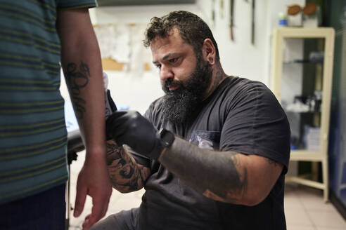 Bearded male artist tattooing on man's hand in studio - SASF00092